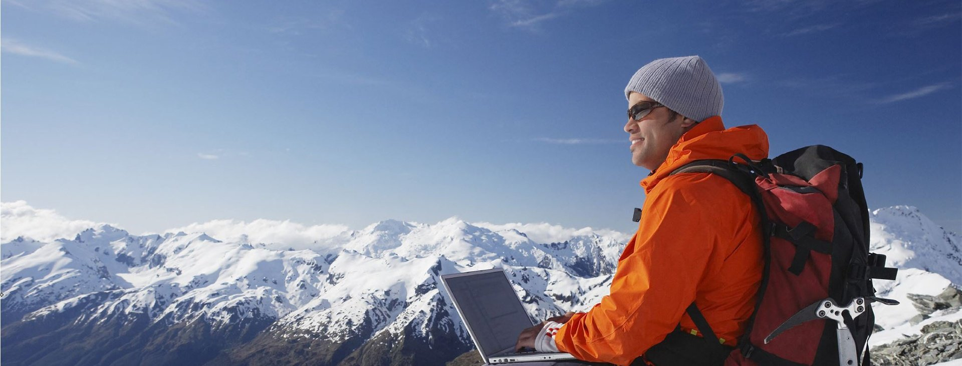 A man with an open laptop sitting with a backdrop of snowy mountain range