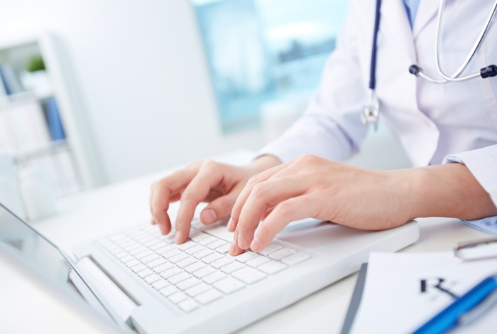 A person with a doctors white coat typing on a computer keyboard